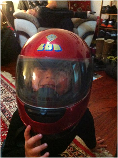 My little buddy Raden at our house wearing one of our motorcycle helmets.